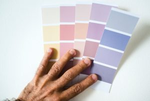 Person holding sorted color palettes